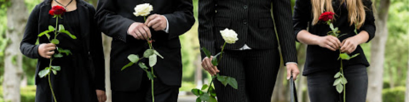 photo of people holding roses at a gravesite