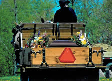 Photo of a casket being driven to the cemetery in the back of an Amish wagon